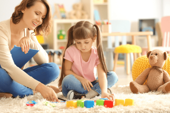 woman and child sitting on floor with colorful blocks