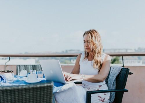 woman working on laptop while sitting outside